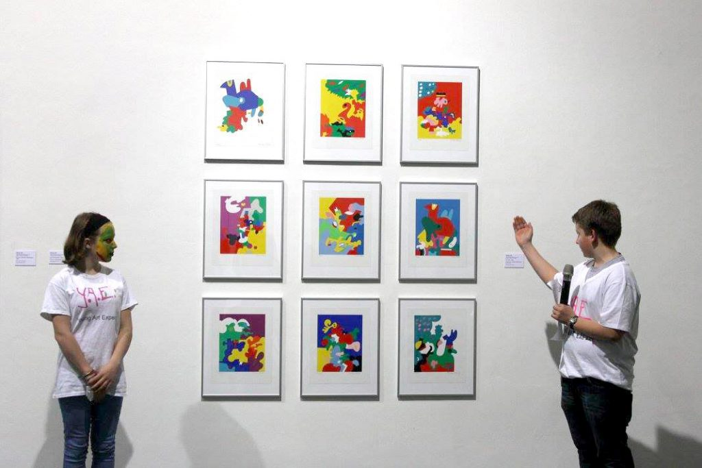 Jugendliche der Young Art Experts-AG vor einer Serie mit Siebdrucken von Ottmar Alt